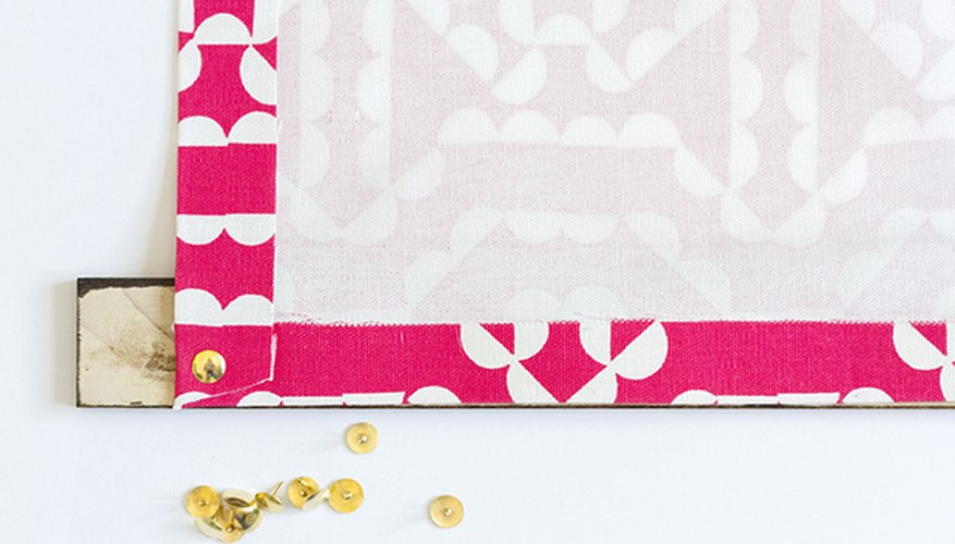 Use thumbtacks or small nails to attach the hemmed fabric to the wooden support.