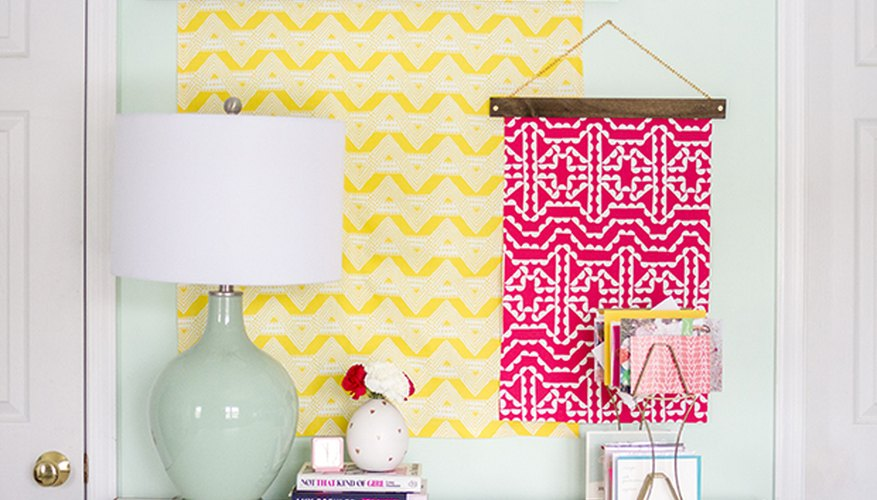 Transform leftover fabric into wall art by adding a wood support and brass chain.
