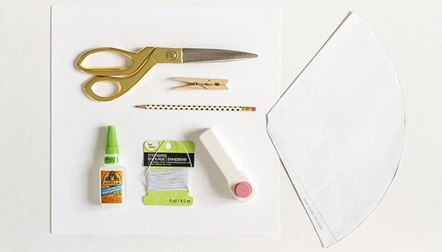Junta los materiales para hacer los gorros de papel.