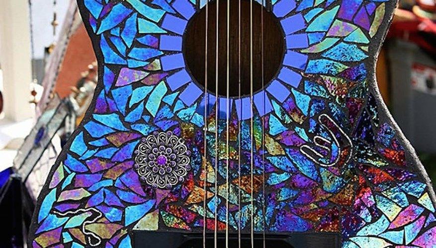 Guitarra acústica decorada con trozos de antiguos discos compactos