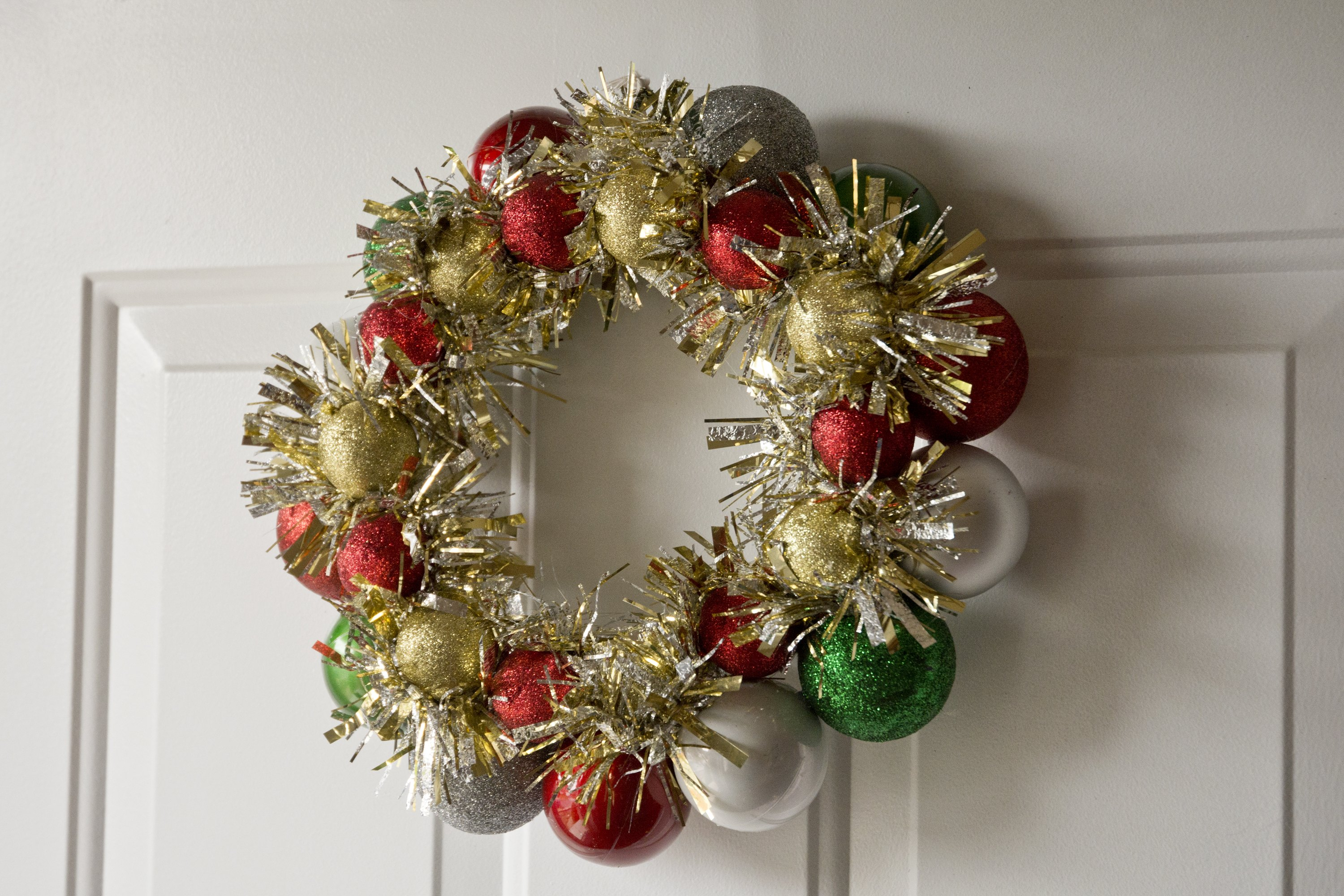 How to Make a Christmas Wreath out of a Coat Hanger by Putting Christmas Balls on It | eHow